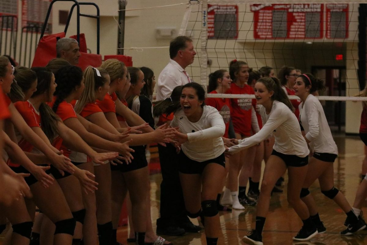Following a win against Holly on Tuesday, senior Libby Carpenter high-fives her teammates.
