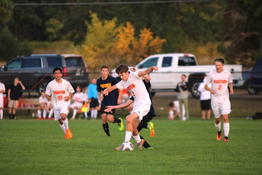 Guarding the ball from his opponent, junior Brady Young participates in the varsity soccer game against Linden. The boys soccer team took home the win against the eagles.