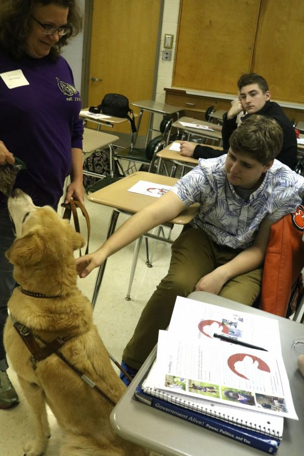 Junior Ben Henley Petting Retired Leaderdog during Career Panel day in Mrs. Muzers classroom. Career Panel day is a day when Fenton High Learns about the jobs they are interested in.