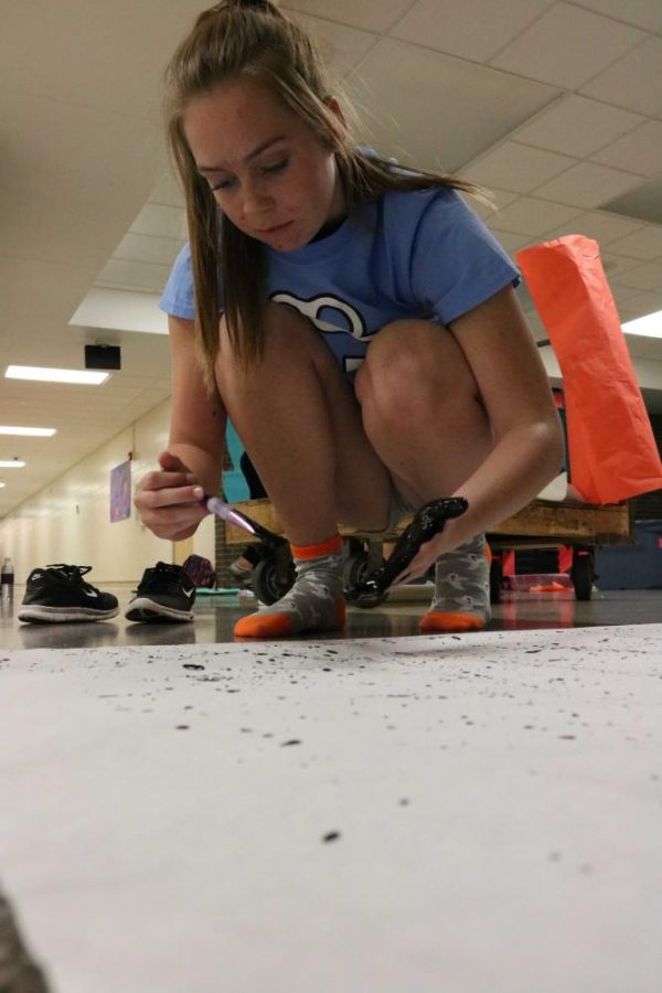 Sophomore Josie Rollier splatters black paint onto the Donkey Kong poster.  Each year during homecoming, the cheerleaders decorate the square to match the theme for each class.