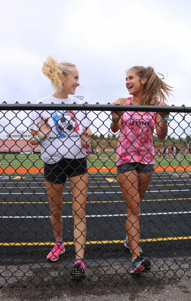On October 4, juniors Abbey Lee and Cami Tieman stretches their legs to prepare to run. The cross country team ran around town then came back to do more workout.