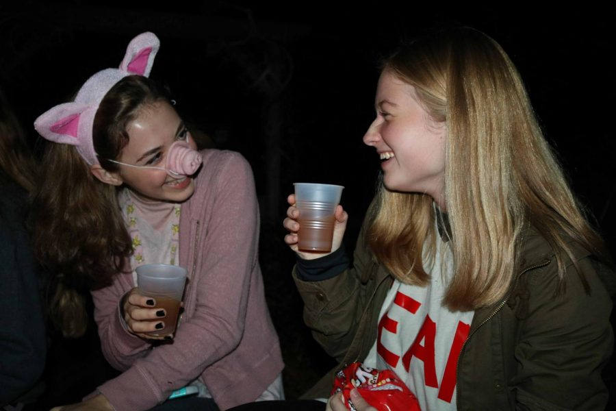 Juniors Sena Haas and Emma Senyko takes a sip of their apple cider at the Photographer Party at the Mead's residence. The Meads organized a hay ride and a haunted house excursion.
