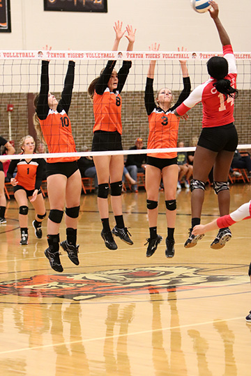 Along side her teammates, sophomore Anna Weigle blocks the opposing teams attack. The girls won the game 3-0.