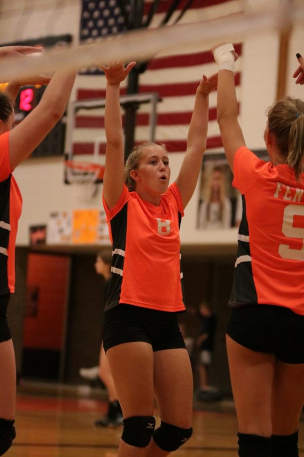 Freshman Mallory Lehman cheers with her team after scoring a point during the volleyball game against Flushing on Oct 10 at home.  They won 3-0.