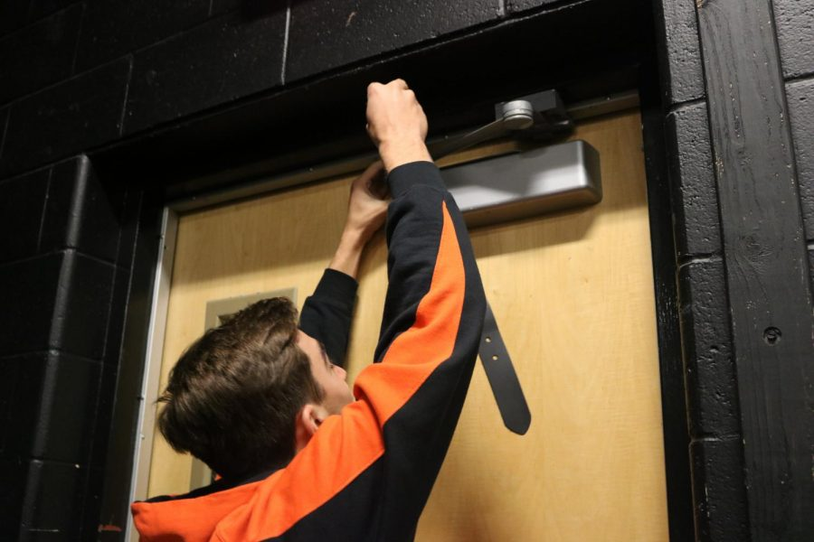 During a lock down drill on Thursday Oct. 19, sophomore Ricky Giltrop puts a belt on the door hinge to help barricade the door. Barricading the door is a portion of the new lock down procedures.
