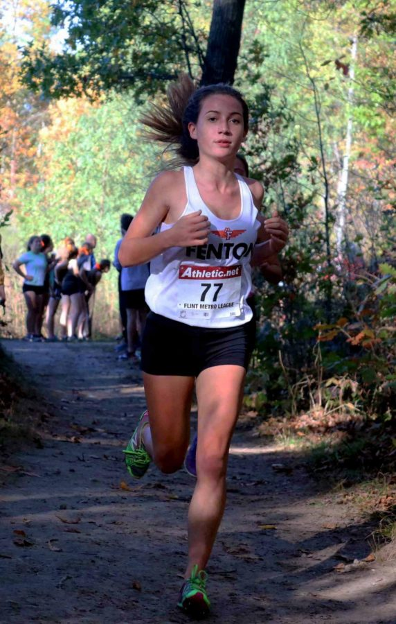 On a Fall Saturday, freshman Kaitlin Bayer runs through the woods to finish her varsity race. The XC teams competed at the Linden High among with several other schools.