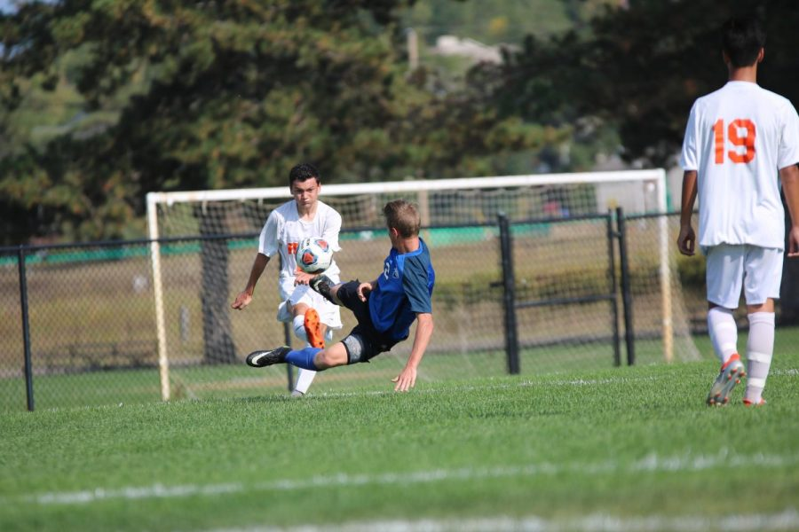 Playing against Genesee Christian, junior Jacob Metras clears the ball avoiding an opponent goal. The boys played a long enduring game in 90 degree weather.