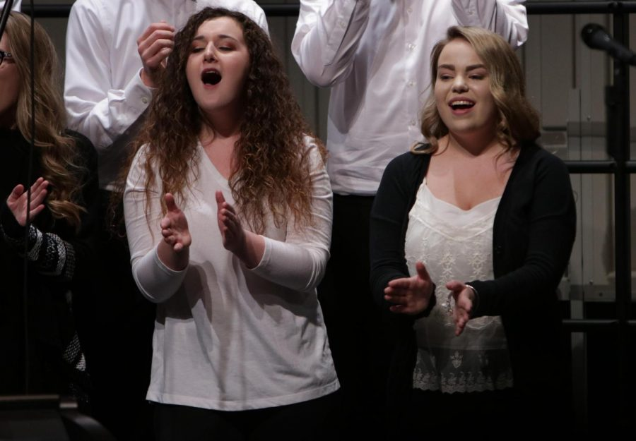 Junior Emily Hayes and sophomore Jenna Maher clap along during the fall informance.  All three choirs, the ambassadors, varsity vocals, and bella voce performed on Oct 24.