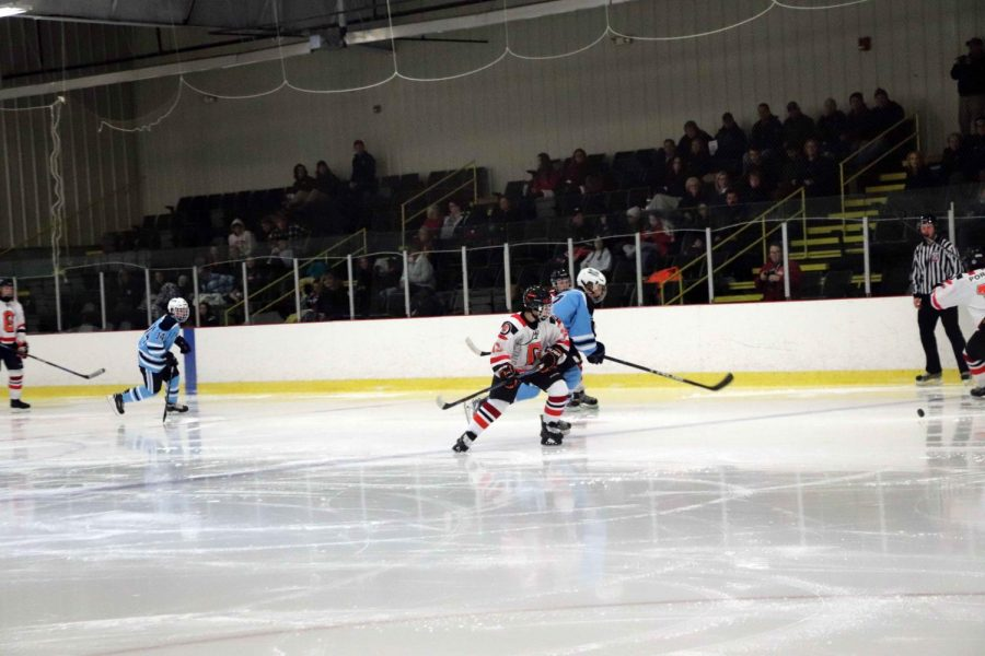 Varsity hockey player, sophomore, Heyden Justus, closes in on Ann Arbor player, racing for the puck during their first game of the season. Their next game is Dec. 3 a 3p.m.