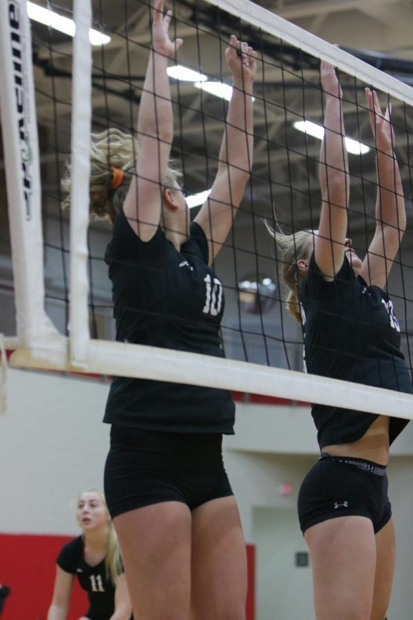 Senior Lily Elfstrom and junior Erin Carter turn away from the net after blocking.