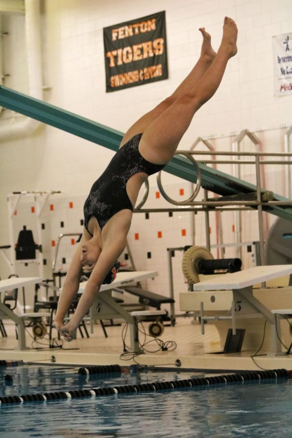Competing against Brandon's swim team, freshman Emma Jump completes a backward dive. The dive team this year is made up of five girls, two of which participate in gymnastics in their off season.