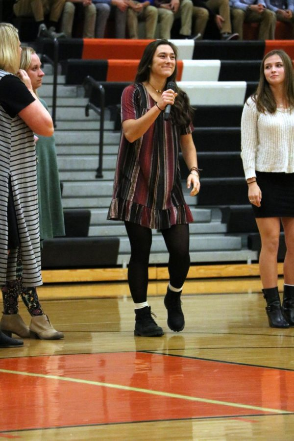 Preparing to introduce her varsity basketball teammates, senior Margaret Berry smiles at the crowd. The girls team took part in the winter meet the team.