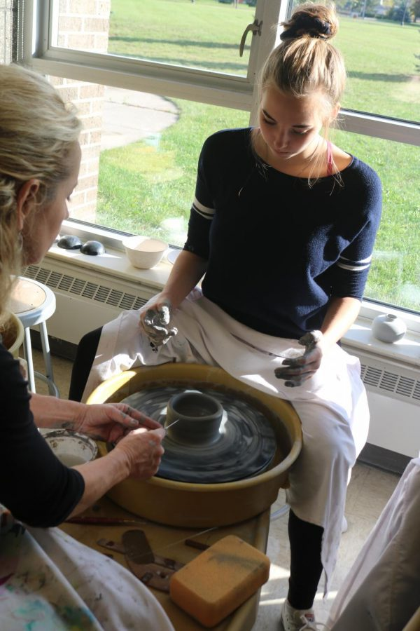 Sophomore Ellie Koester works on a pottery wheel with art teacher Teresa Moss on a clay bowl.  Students join Moss during SRT to learn how use the pottery wheel.