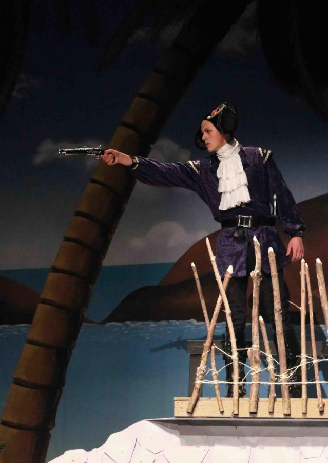 Senior Tyler Dunn aims his weapon as he acts in the school play Treasure Island. The students had very successful performances of the play and had a lot of fun making it.