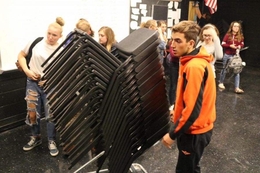 Moving chairs to put in front of the door, sophomore Ricky Giltrop works to create a blockade during the drill.