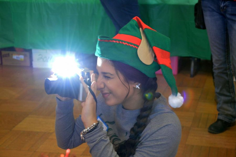 While volunteering at the Lunch with Santa, junior Zena Alshomali takes pictures of the kids getting to meet Santa. The lunch is put on by the Kiwanis Club and the Key Club members from the surrounding high schools have the chance to volunteer their time.