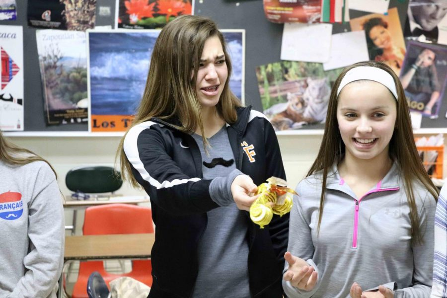 Freshman, Jordan Wensley hands Sadie Wills a sack of chocolate gold. On Thursday, December 7, french one had a party. They all gathered in a circle and play hot potato with sack of gold.