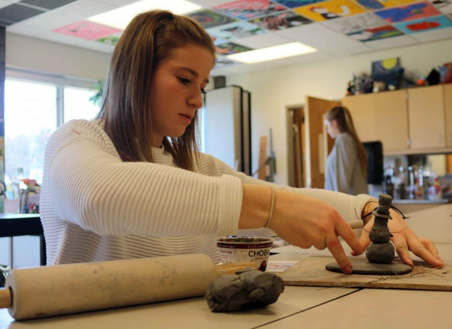 Senior Julie Celini adjusts the base of her clay snowman for her advanced art class. The advanced art students were assigned a project to recreate a 3D holiday postcard.