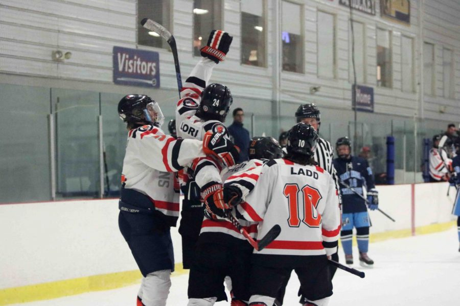 After scoring a goal, sophomore Nate Ladd, junior Joe Loria,sophomore Elliot Wakeham, and senior Jake Thompson celebrate in a group hug. The Griffins had their first win Dec. 6, with a score of 5-2.