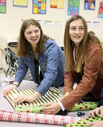 In Mrs. Muzer's SRT, sophomores Ally Rensi and Trinity Sawyer wrap gifts. Their SRT was assigned an angel tree child to buy presents for and to give to them.