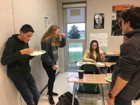 On their last day before Christmas break, juniors Jack Killian, Kyle Bliss, Julia Stocker and Parker Bundy eat food that was brought in for their IB history party. While enjoying the food that was brought in, the students were also assigned to create a mural documenting Latin American Independence.