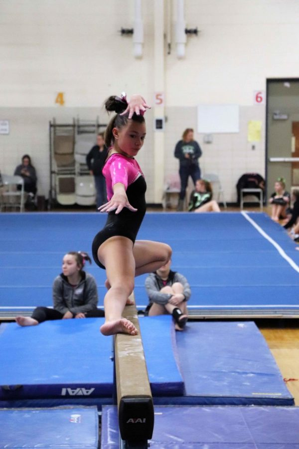 Trying to keep balance on the beam, freshman Lauren Hayden performs her balance beam routine during the teams most recent competition. The girls varsity gymnastics team is composed of girls from Fenton, Lake Fenton, and Linden schools.