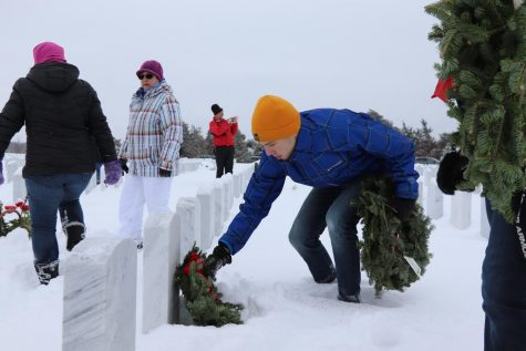 Basketball teams volunteer by placing wreaths at National Cemetery