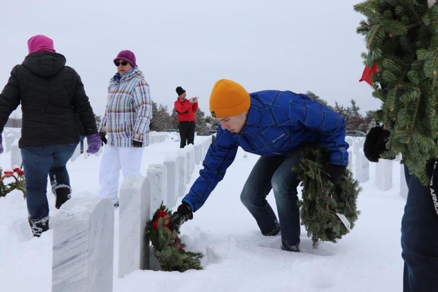 Basketball teams volunteer by placing wreaths at National Cemetery