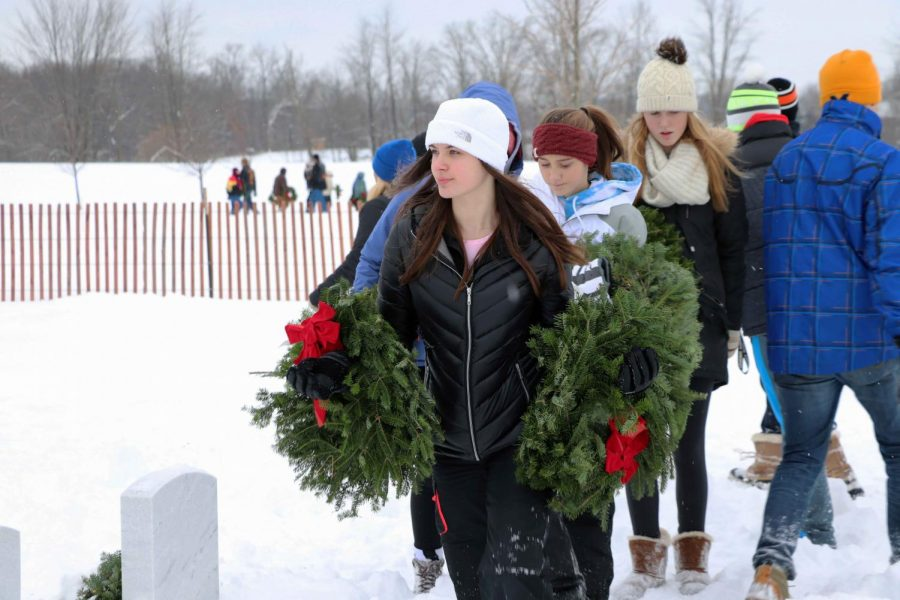 Volunteering her time freshman Riley Spock carries her wreaths down the path looking for a empty gravestone. This past Saturday the Fenton basketball teams volunteered their time at the Great Lakes National Cemetery by honoring veterans who are laid to rest there by placing wreaths on their graves.