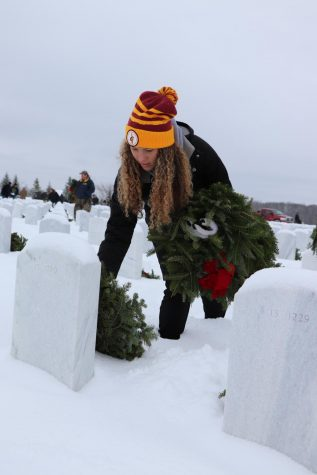 Junior Kirsten Foor lays a wreath on a grave. The boys and girls basketball teams went to the Great Lakes National Cemetery in Holly to lay wreaths for the holiday season.