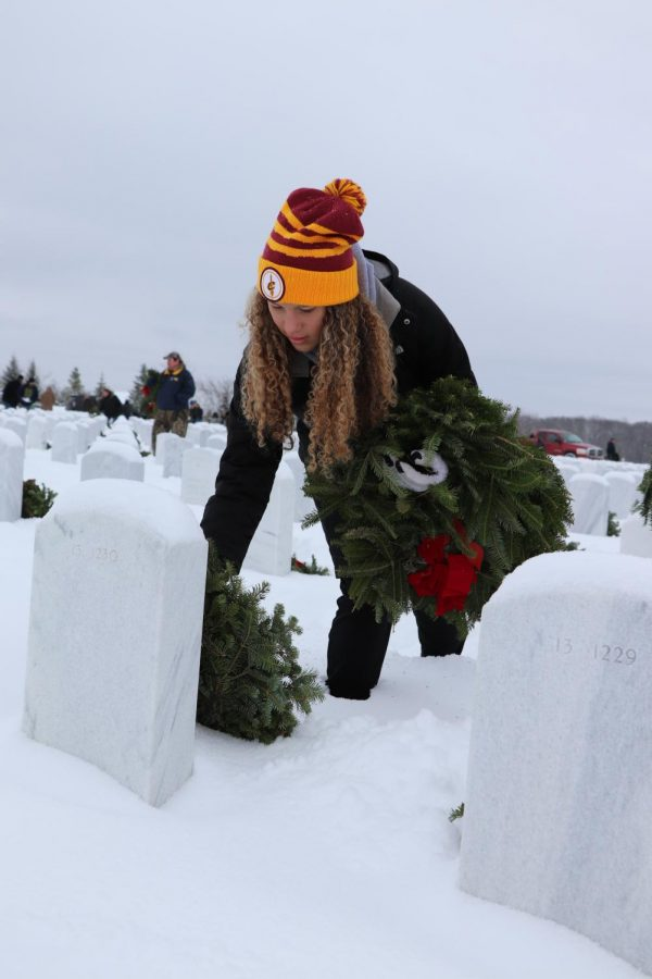 Junior+Kirsten+Foor+lays+a+wreath+on+a+grave.+The+boys+and+girls+basketball+teams+went+to+the+Great+Lakes+National+Cemetery+in+Holly+to+lay+wreaths+for+the+holiday+season.