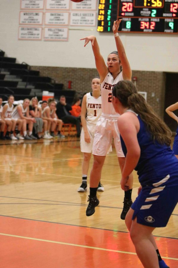 Playing in the first home varsity girls basketball game, senior Margret Berry shoots the ball at the basketball. The girls played against White Lake Lakeland and won with the score of 56-26.