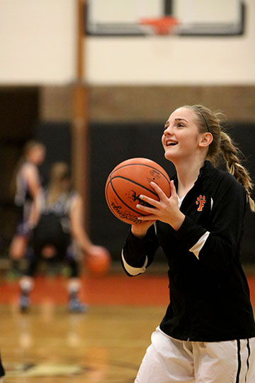 Before the basketball game, sophomore Brie Sanford shoots a practice free throw. The girls JV team played Brandon High School.