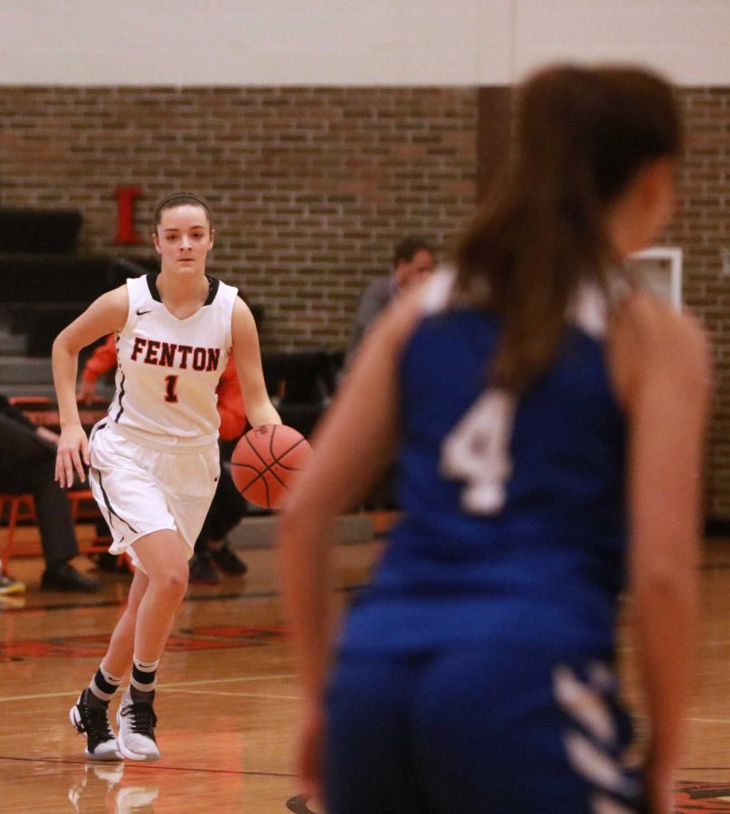 During the varsity girls basketball game, junior Erin Conroy dribbles the ball down the court to score against the opposing team. The girls played White Lake Lakeland on Dec. 5 and won 56-26, a to start their basketball season.