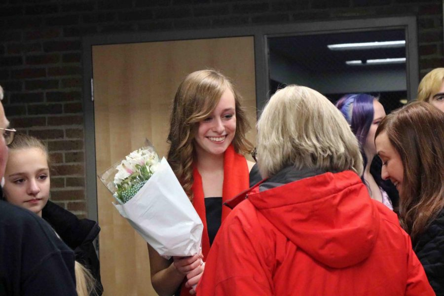 After preforming in the holiday choir concert, sophomore Emily Wright receives flowers from her family. At the performance the choirs performed songs separately and all together.