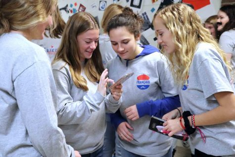 Junior Maddie Hayden shows her fellow IB French friends something on her phone. All of the french classes got their picture taken in front of the mural. They did this for the St. Nicholas Day french party.