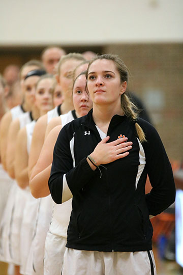Standing for the National Anthem, sophomore Abby Skinner prepares for her game. The girls won 38-34 against Clio on Tuesday Dec. 19.