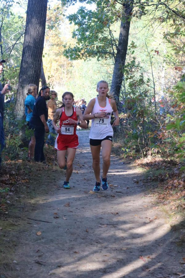 Keeping the lead, sophomore Alexa Keiser runs as a competitor trails behind her.