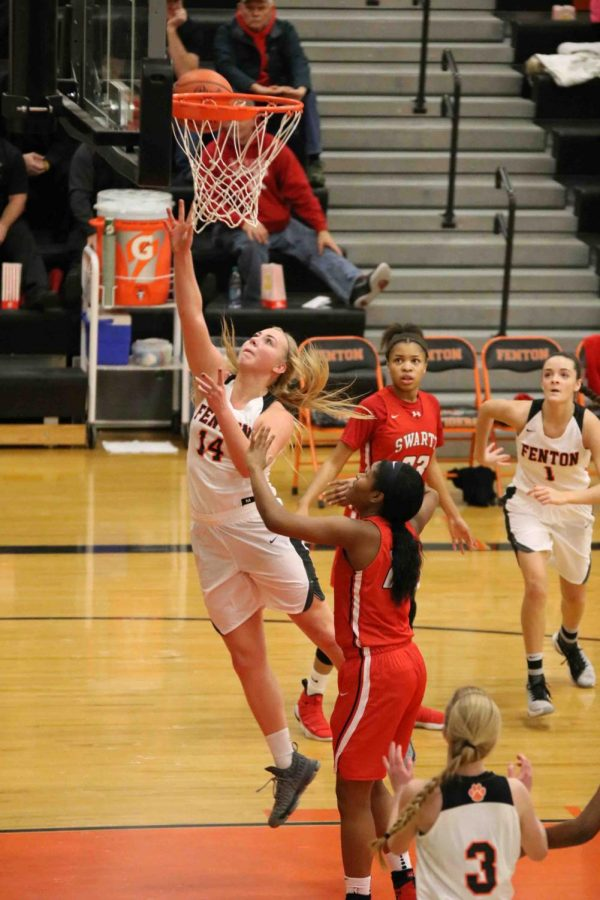 Completing a layup, junior Chloe Idoni plays with her teammates against the Swartz Creek Dragons. The girls played a good game and came out on top with a score of 77-47.