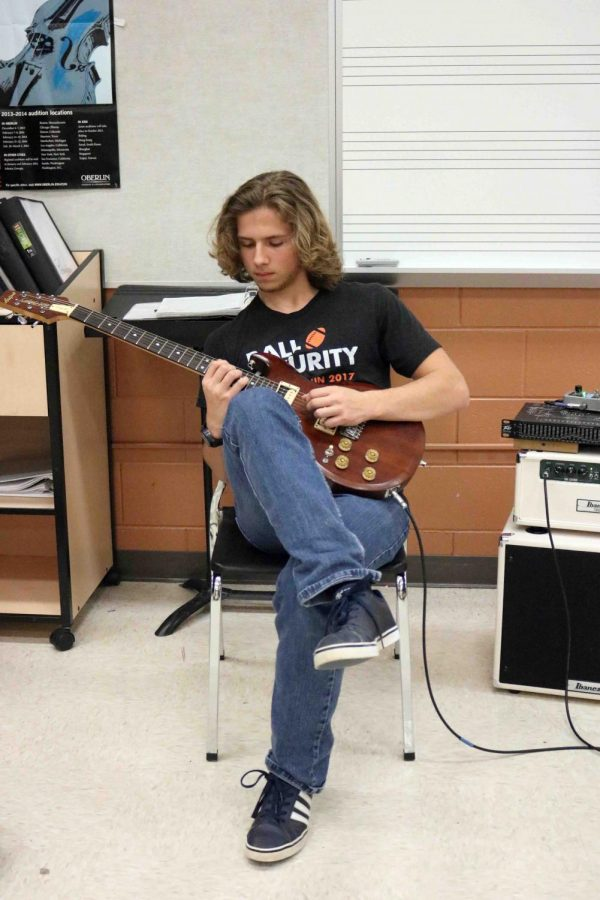Senior Tatum Foster plays the guitar with his fellow band members. A group of students from the wind ensemble and the jazz band played together on December 22.