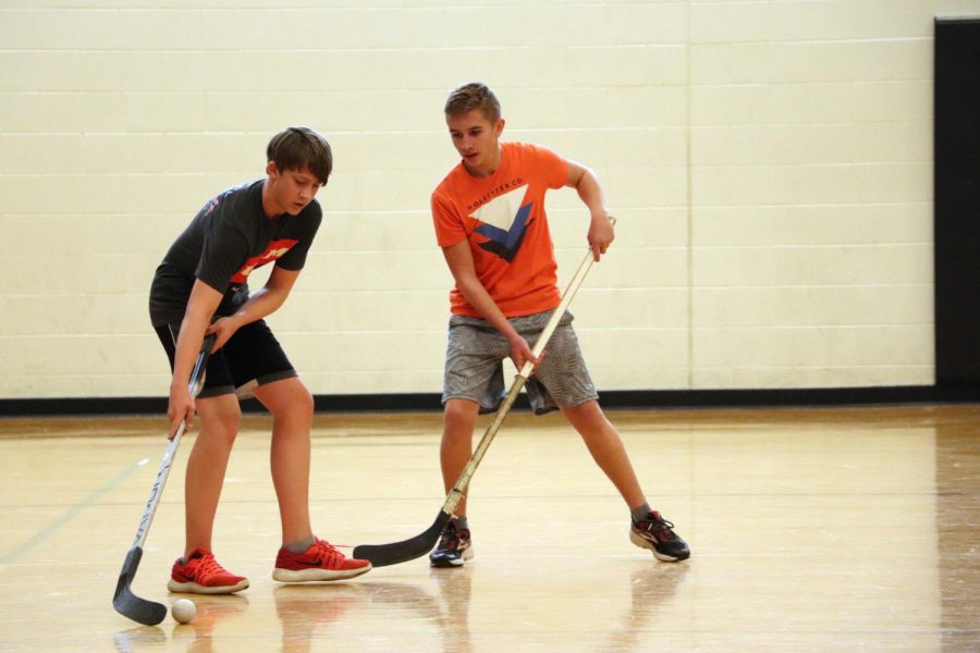 Freshman Landen Day defends the ball Cooper Patridge while playing floor hockey in gym class.  The freshmen classes played floor hockey on Jan. 8 and 9.