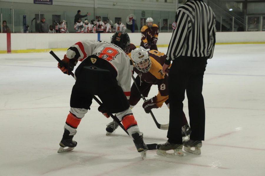 Fenton high school senior, Jake Tompson gets up close and personal at December 25's home game. Ready to fight for the puck, readying himself in hopes of moving faster than his opponent.