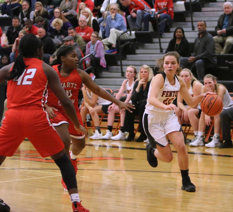 Senior, Maddie Carr dribbles around her opponents from Swartz Creek. The varsity girls basketball team won the game against Swartz creek, 77-47 on Dec. 8.