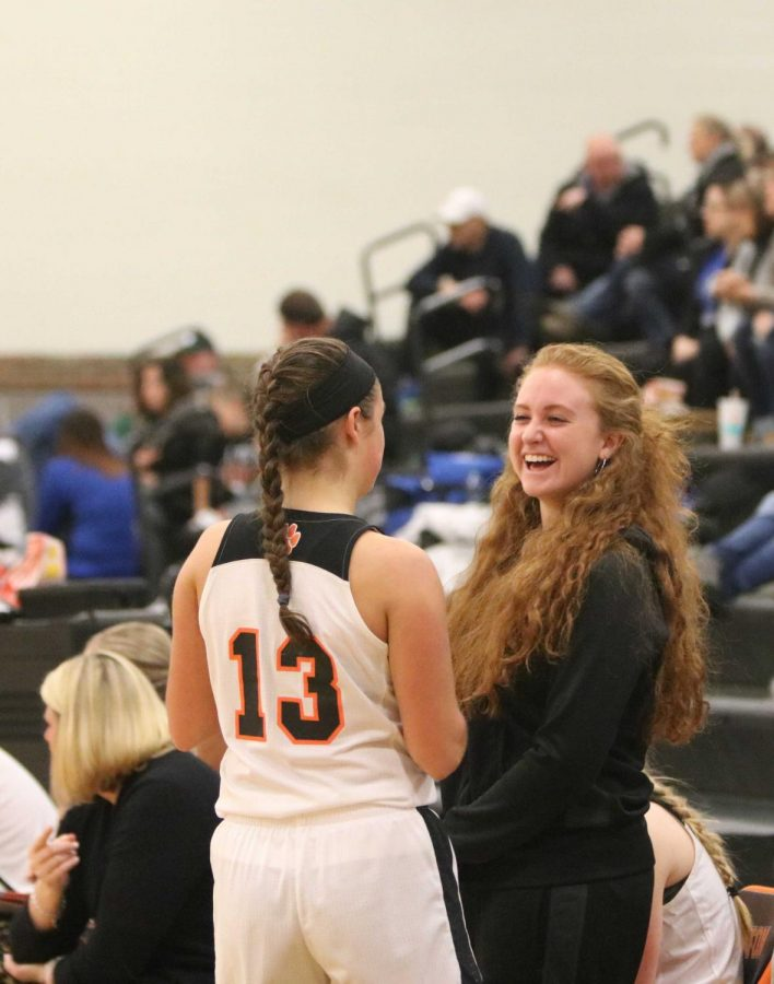 Junior Sophie Frost jokes around with teammate, senior Aly Lenz after coming back off of the court. The girls finished the game  with a victory against Brandon, 59-25.