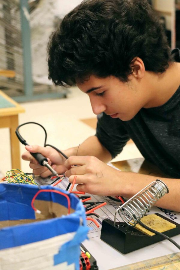 Sophomore Vaughn Doyle concentrates on soldering wires connections together for the Robotic's Team new robot.The Titanium Tigers first competition will be on Mar. 2.