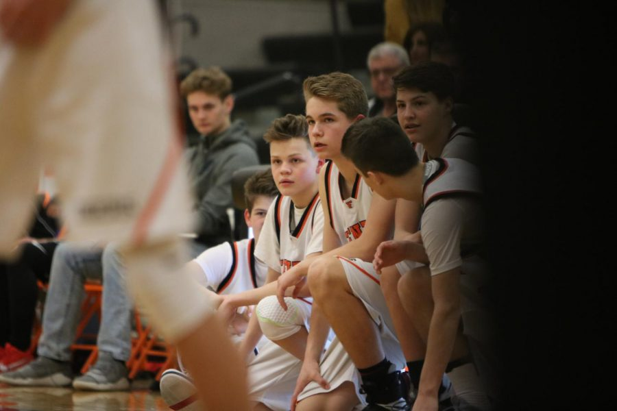 Watching his teammates as the clock ticks down, freshmen Carter Frost watches along the sidelines till it's his time to go in the game. The freshmen boys basketball team beat their rivals, Linden, Feb. 22, 58-34 in one of their last home games of the year.