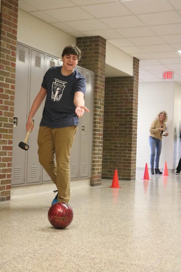 Along with his physics class, junior Ben Henley bowls with his group. Students are learning the physics that are involved bowling.
