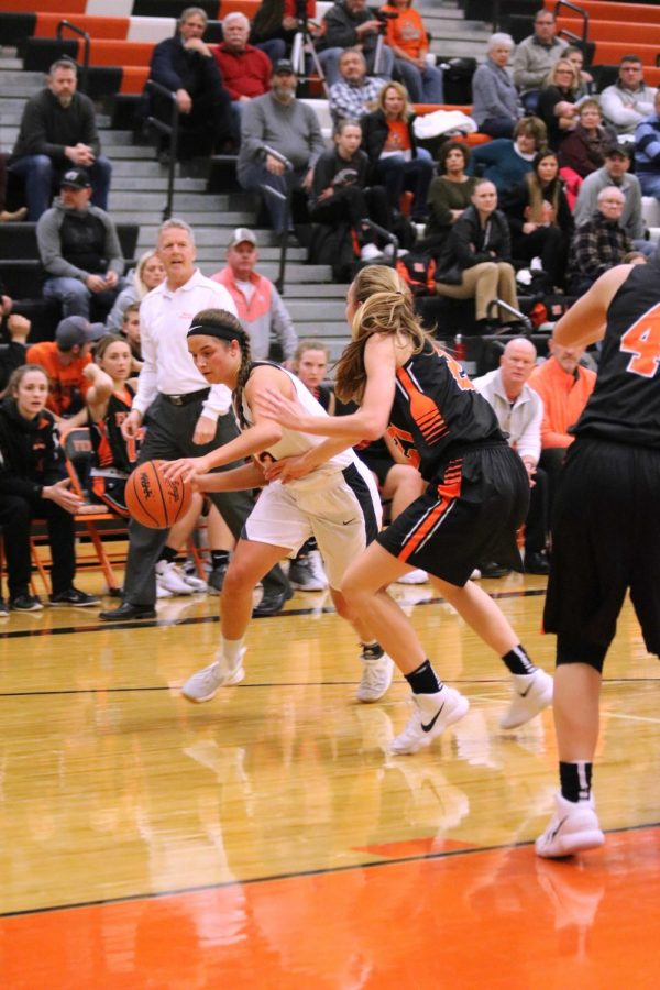 Keeping the ball away from her opponent, senior Aly Lenz plays against Flushing. The girls varsity basketball team gave the Raiders their first loss since joining the league, making their record now 54-1. Congratulations to the team and to their coach Rebecca Moore.