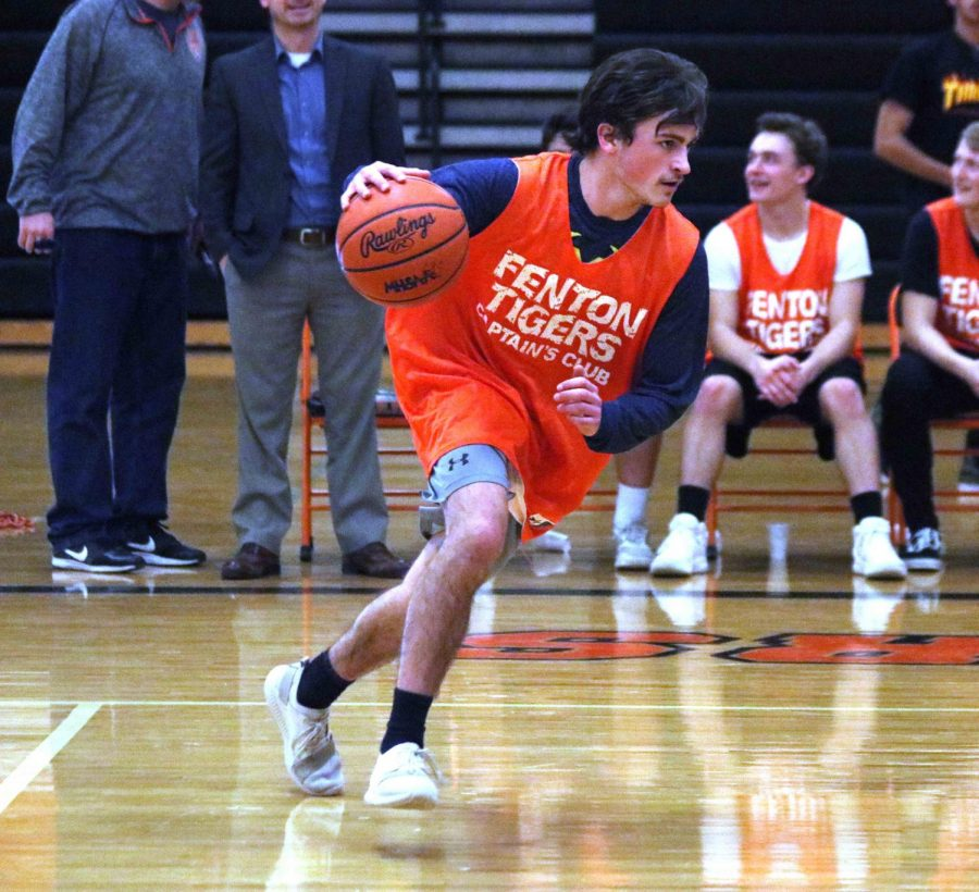 Senior Cameron Hartley runs down the court with the ball in his hand ready to shoot a basket. Members of Captains Club played basketball against students from Knopf Learning Center.