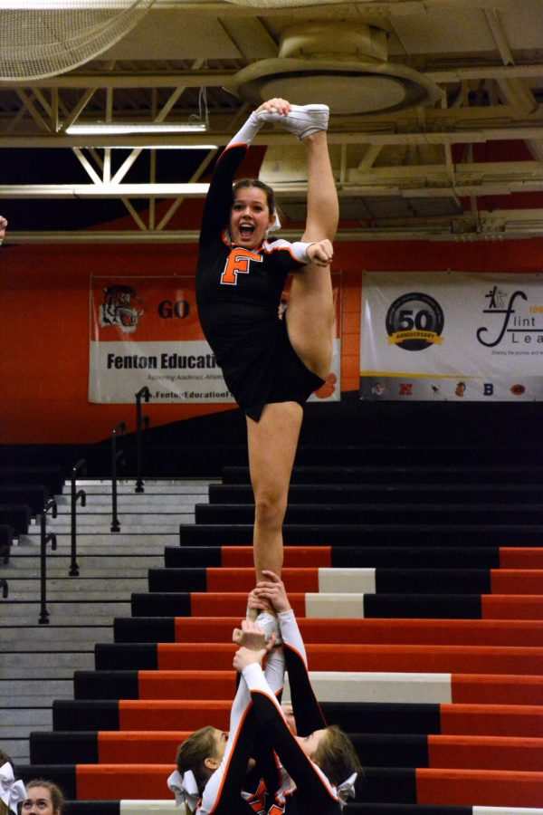 Performing in front of the judges, freshman Taylor Wire executes her stunt alongside her team. The girls compete in a total of three rounds per competition.